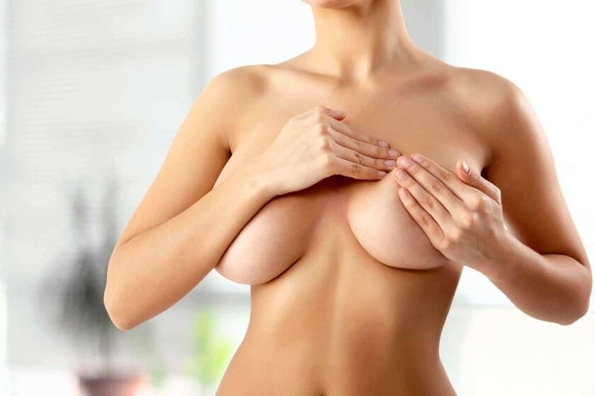 Woman holding her breasts