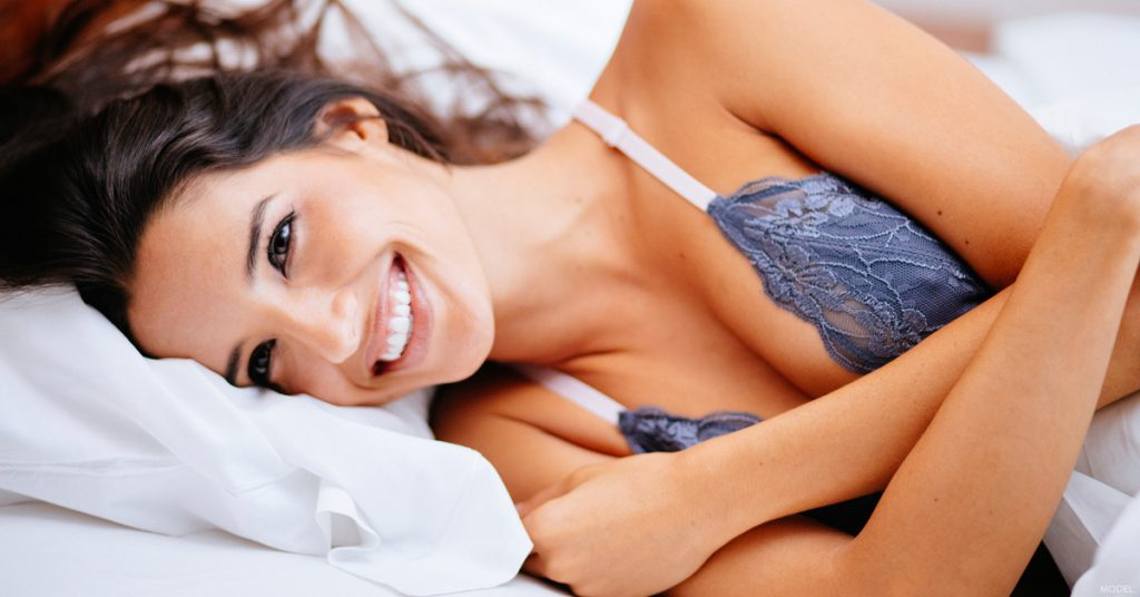 Woman lying in bed considering breast reduction options in The Woodlands, Texas
