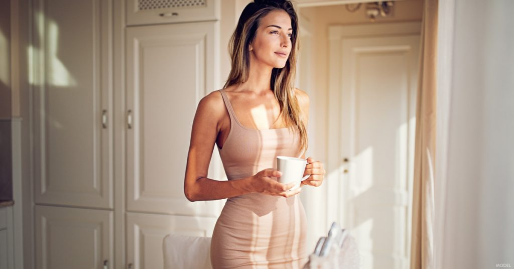 Woman with great curves in The Woodlands, TX holding coffee mug looking out window