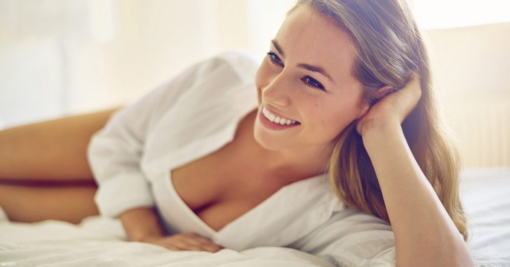 Smiling woman with head resting on hand in blouse revealing cleavage