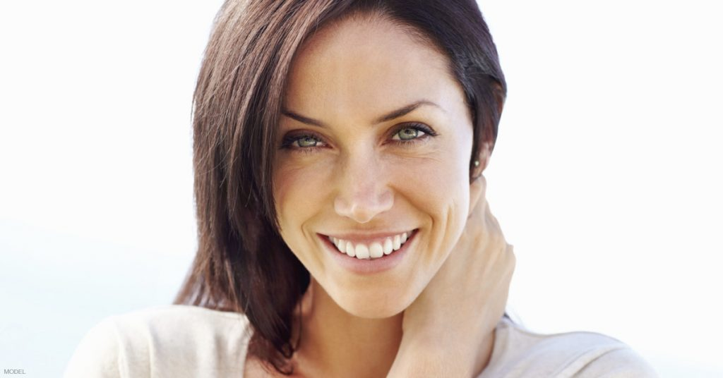 Woman with short brown hair smiling, with her hand on side of her neck